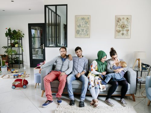 Portrait: Anaïs, Vincent, and their son César, host Afghan refugees Zulfeqar and Battarine, in Saint-Priest, France.